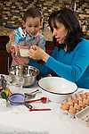 3 year old boy in kitchen at home with mother learning to cook baking, looking at level of non-dairy milk in measuring cup