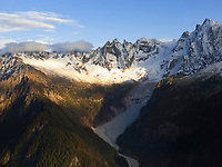 Switzerland. Canton Graubünden. Bregaglia valley. Aerial view on the mountains above  Bondo. The village was hit by three massive landslides caused by a giant rockslide swept down from Piz Cengalo on August 23, 2017. Right to left: The mountains' names are Piz Badile (3308 m), Piz Cengalo (3369m), Piz dei Gemelli (3259), Sciora Dadent (or Sciora di Dentro) (3,275 m). 20.09.2017 © 2017 Didier Ruef