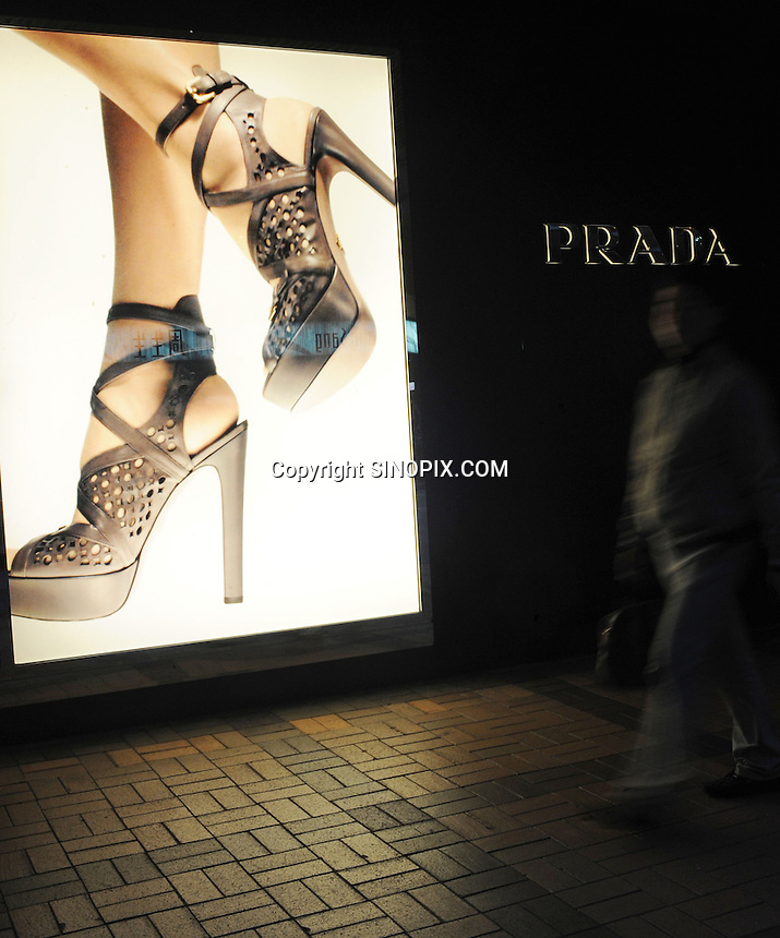 People walk pass Prada shop in Hong Kong. Hong Kong, with its leading position as an international centre for luxury fashion brands carry the complete range of one of the world's top fashion brands products. .