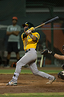 AZL Athletics catcher Cesarre Astorri (11) follows through on his swing during an Arizona League game against the AZL Giants Black at the San Francisco Giants Training Complex on June 19, 2018 in Scottsdale, Arizona. AZL Athletics defeated AZL Giants Black 8-3. (Zachary Lucy/Four Seam Images)