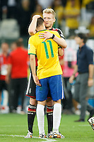 Oscar of Brazil is consoled by Chelsea team mate Andre Schurrle of Germany