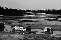 """Iranduba, Amazonas 29 09 20100 MEIO AMBIENTE SECA. Vista da cidade de Manaus a partir do porto de Cacau Pirera. Casa flutuantes encalhadas no que restou do igarapé na maior estiagem do rio Negro. A série """" Seca no Amazonas"""", documenta  a maior seca já registrada no  estado desde que  o nível dos rio Amazonas e rio Negro passaram a ser monitorados em 1905. Eventos extremos estão se tornando cada vez mais comuns para a população que tenta adaptar-se a a cada período de estiagem na região. (Foto Alberto Cesar Araujo)"""