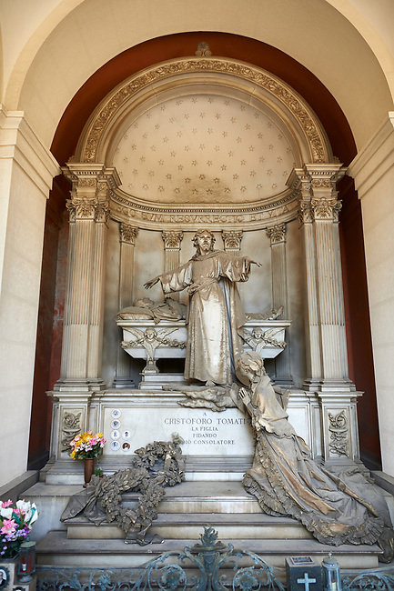 Picture and image of the stone sculpture of Christ standing arms outstretched by the sacophagus of the deceased whilst his wife prays on the steps of the tomb. Sculpted in a Borgeoise Realistic style by GB Villa in 1881. The Tomati family tomb, section D no 12, the  monumental tombs of the Staglieno Monumental Cemetery, Genoa, Italy