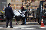 The body of a COVID-19 victim is wrapped up after being removed from a refrigerated trailer serving as a temporary morgue during the coronavirus pandemic (COVID-19) in front of New York Community Hospital in the Brooklyn borough of New York City on April 5, 2020.  Photograph by Michael Nagle