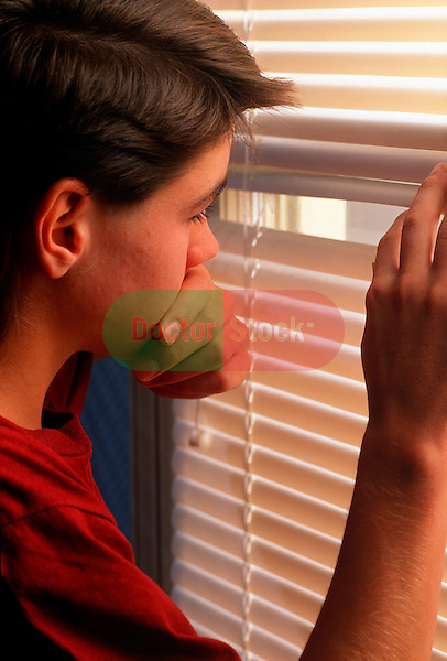 teenage boy suffering with anxiety looking out venetian blind of bedroom window
