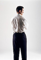 Caucasian looking man wearing a white shirt with his back to camera