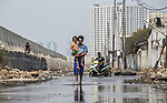 13 August 2019, Jakarta, Indonesia: Facory worker Dodi Riyanto with his daughter Ulfi walks along the flooded road in front of his home below the sea wall at Muara Baru, North Jakarta.The protective seawall barrier keeping the ocean at bay was built by Governor (now President) Joko Widodo. It was constructed to prevent further encroachment by the ocean into the settlements in North Jakarta which is sinking at a rate faster than anywhere else in the world. Residents speak of the flooding  that would drive them to higher ground washing away all in its path. Residents now say the land is dry and usable but it is an ongoing crisis for Indonesia. Picture by Graham Crouch/The Telegraph
