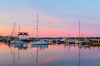 Pleasure boats and commercial fishing boats moored and docked in Menemsha Basin under a colorful pre-sunrise sky, in the fishing village of Menemsha in Chilmark, Massachusetts on Martha's Vineyard.