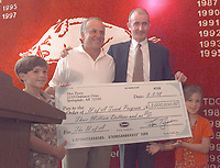 Arkansas Democrat-Gazette/WILLIAM E. THOMPSON--8-8-98--John Tyson presents a check for $3,000,000 to John McDonnell, University of Arkansas' head coach for track and field, with his two childern John Randel Tyson, 6, left, and Olivia Tyson, 6, during a press confrence at Bud Walton Arena Saturday afternoon. The money will be used to build the Randal Tyson Indoor Track and Field Complex.