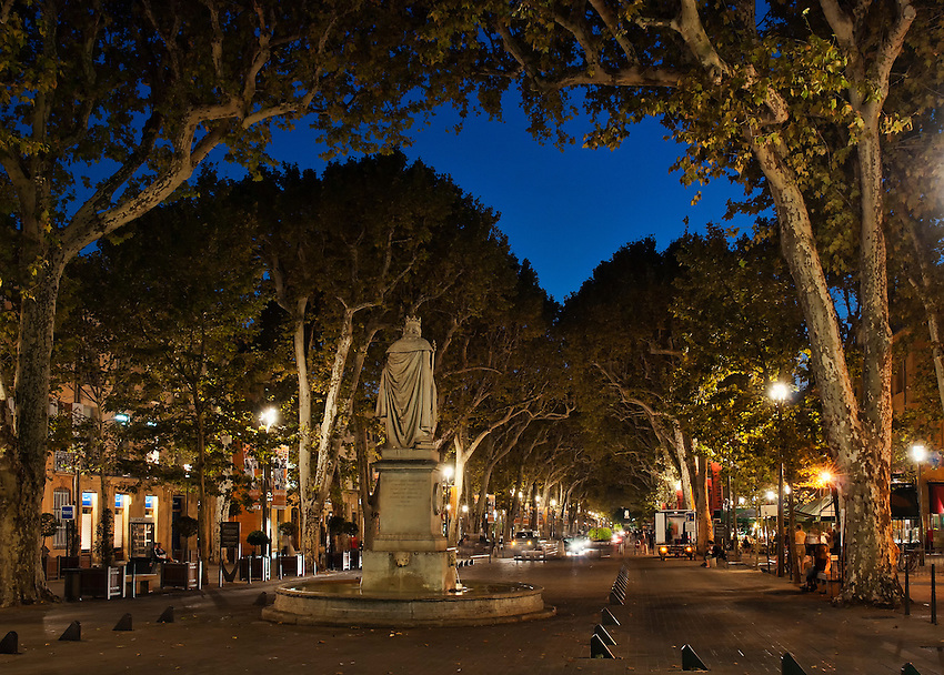 """Early evening view down the Cours Mirabeau, Aix-en-Provence, France, during the """"blue hour,"""" including the fountain and statue of King Rene"""