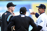 Asheville Tourists manager Joe Mikulik #20 goes over the ground rules and exchanges lineups with Delmarva manager Ryan Minor and umpires Charlie Tierney and Ryan Bealo  before a game between the Delmarva Shorebirds and the Asheville Tourists April 6, 2012. The Shorebirds won the game 7-2  (Tony Farlow/Four Seam Images)..