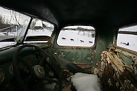 Mike Williams drives his team past an old abandoned Ford truck as he arrives at the Anvik checkpoint.  2005 Iditarod Trail Sled Dog Race.