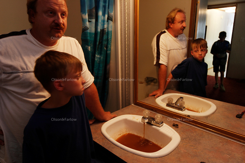 """Kenny Stroud and sons Chase and Aaron react to the orange/black water in the bathroom that smells and has an oily residue mixed with coal soot. <br /> <br /> Kenny's health is affected and he fears for his sons. Kenny reacts with rashes and red eyes when he showers. He tells the kids """"Don't brush teeth in water. Don't drink the water."""" <br /> <br /> When he moved in six years ago he thought the only problem was that the water was discolored by iron. Stroud, 38, developed gallstones, breathing problems, memory loss, and his hair is falling out. He has anxiety, nervousness and his pancreas is at two percent function. All of this occurred after he moved to this trailer. Scared for his family, he asks, """"What have I done to them?"""" Neighbors in nearby Williamson and Rawls who have the same water are having it analyzed. <br /> <br /> A November 4, 2003 Associated Press article by Michelle Saxton of the Williamson Daily News entitled """"Water in Mingo Communities Contains Manganese"""" stated that some security guards quit opening valves on Massey pumps when they realized they were poisoning the community. In a later court hearing it was shown that Massey Coal Company had, indeed, Illegally injected slurry from the Rawls Sales Processing Company (Massey Coal Company subsidiary) impoundment into abandoned underground mines for at least eight years."""