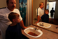 "Kenny Stroud and sons Chase and Aaron react to the orange/black water in the bathroom that smells and has an oily residue mixed with coal soot. <br /> <br /> Kenny's health is affected and he fears for his sons. Kenny reacts with rashes and red eyes when he showers. He tells the kids ""Don't brush teeth in water. Don't drink the water."" <br /> <br /> When he moved in six years ago he thought the only problem was that the water was discolored by iron. Stroud, 38, developed gallstones, breathing problems, memory loss, and his hair is falling out. He has anxiety, nervousness and his pancreas is at two percent function. All of this occurred after he moved to this trailer. Scared for his family, he asks, ""What have I done to them?"" Neighbors in nearby Williamson and Rawls who have the same water are having it analyzed. <br /> <br /> A November 4, 2003 Associated Press article by Michelle Saxton of the Williamson Daily News entitled ""Water in Mingo Communities Contains Manganese"" stated that some security guards quit opening valves on Massey pumps when they realized they were poisoning the community. In a later court hearing it was shown that Massey Coal Company had, indeed, Illegally injected slurry from the Rawls Sales Processing Company (Massey Coal Company subsidiary) impoundment into abandoned underground mines for at least eight years."