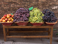 Fresh grapes and nectarines in wicker baskets outside shop in Siena, Ital