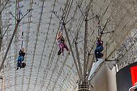 Las Vegas, Nevada.  Fremont Street.  Three Young Women Riding the SlotZilla Zipline.