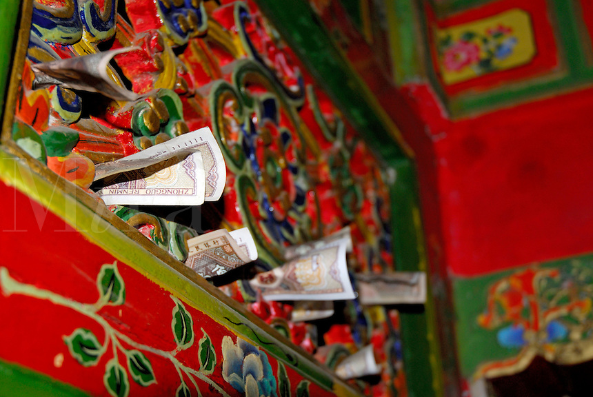 Donations of Chinese bills, renminbi, rolled into nooks on a painted carving above an apartment doorway at Ganden Palace, residence of past Dalai Lamas, Drepung Monastery, Lhasa, Tibet, China.