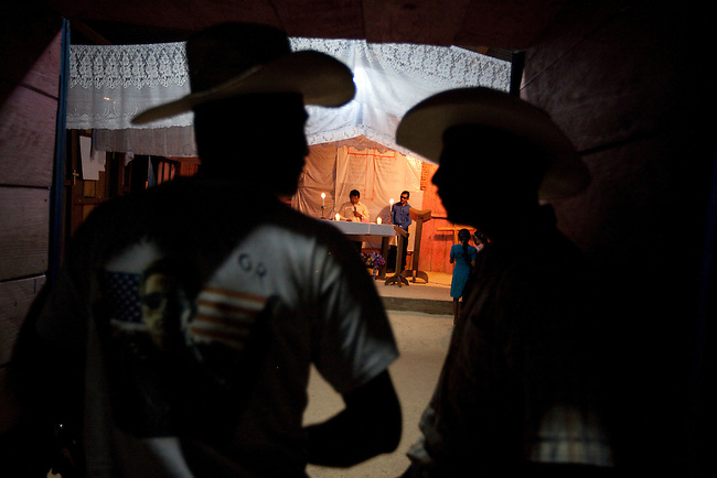 Men outside an evangelic church at an illegal settlement in the Mayan Biosphere.