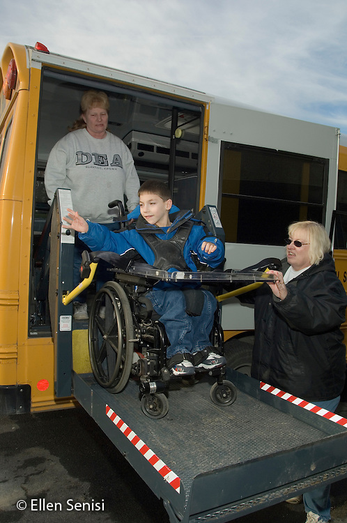 MR / Albany, NY.Langan School at Center for Disability Services .Ungraded private school which serves individuals with multiple disabilities.Child waves goodbye as he boards schoolbus using wheelchair lift operated by school bus driver and assisted by bus aide. Boy: 9, cerebral palsy, limited verbal output with expressive and receptive language delays.MR: Rub1, Lyo3, Zie1.© Ellen B. Senisi