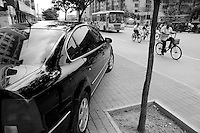 Black car parked on the sidewalk as people on bicycles ride past, Datong, Shanxi, China.