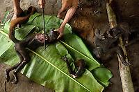 Conta Wadeca, a Waorani (Huaroni) woman, chops up a roasted monkey on a banana leaf.