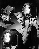 Student preparing to take picture with M-R spotlights sample of student work at NTS (photography) Pensacola.  Date: Received, July 24, 1944.