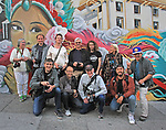 """A group of photographers from """"Friends of Photography"""" pose in against a mural in Chinatown, San Francisco, CA."""