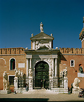 The Porta Magna of the Venetian Arsenal. Capped by the lion of St Mark, the Arsenale's land gate is considered by many to be the earliest example of Renaissance architecture in Venice; it was probably executed in 1460. A plaque on the wall celebrates the 1571 victory at Lepanto, and at the foot of the gate is a row of carved lions; the biggest one, regally seated, was taken as booty by Francesco Morosini from the Greek port of Piraeus.