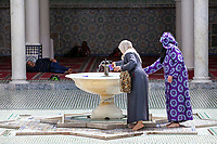 Fes, Morocco.  Women Getting Water for Ablutions, Mausoleum of Moulay Idris II, Fes El-Bali.
