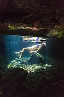 A woman explores a collapsed lava tube swimming hole on the Big Island of Hawai'i.