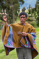Peru, Urubamba Valley, Quechua Village of Misminay.  Village Man Performing a Welcoming Ceremony for Guests, Sprinkling Chicha to the Spirits.