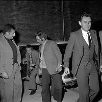 """Double crime d'Ondes. Les assassins keller et Horneich <br /> <br /> """"+ M. Dalas chef du SRPJ"""" 4 octobre 1972. Vue d'ensemble de Marcellin Horneich, menoté et entouré des policiers chargés de l'enquête, vient de sortir d'une voiture. Cliché pris le lendemain de l'arrestation des deux suspects Joseph Keller et Marcellin Horneich dans l'affaire du double meurtre d'Ondes. Observation: Dans la nuit du 29 au 30 août 1972, un couple de touristes anglais autostoppeurs, est assassiné à Ondes (José Clive Latter 23 ans et Joy Joffe 20 ans). Un mois après, les auteurs du crime sont interpelés : ils s'agit de Marcellin Horneich et son neveu Joseph Keller. Ils avouent leur crime le 4 octobre 1972. Après 4 ans d'instruction, ils sont condamnés à mort le 25 juin 1976 par la Cour d'Assises de la Haute-Garonne. Le 8 janvier 1977, ils sont tous les deux graciés par le Président Valéry Giscard d'Estaing."""
