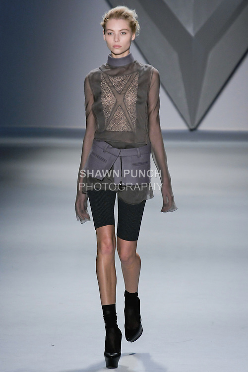 Vika Falileeva walks runway in a steel silk chiffon crisscross appliqué and net lace long sleeve top with stand melton collar, with charcoal rib knit bermuda short with steel melton zip-front peplum, from the Vera Wang Fall 2012 Vis-a-gris collection, during Mercedes-Benz Fashion Week Fall 2012 in New York.