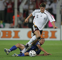 Italian midfielder (16) Mauro Camoranesi slides under German defender (5) Sebastian Kehl.  Italy defeated Germany, 2-0, in overtime in their FIFA World Cup semifinal match at FIFA World Cup Stadium in Dortmund, Germany, July 4, 2006.