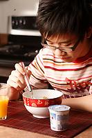 MODEL RELEASED PHOTO.<br /> A fourteen (14) year old asian male teenager, from China eat a breakfast made of cereal, yogourt and orange juice<br /> <br /> Un jeune adolescent de quatorze (14) ans d'origine Chinoise mange un déjeuner composé de céréales, yogourt et jus d'oranges. <br /> <br /> Photo : Pierre Roussel / Images Distribution