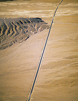 aerial photograph of a long empty stretch of road in Death Valley National Park, northern Mojave Desert, California