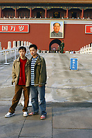 CHINA. Beijing.  Tourists stand in front of the famous Mao Zedong portrait that hangs on the 'Gate of Heavenly Peace' which leads into the Forbidden City and is opposite Tiananmen Square. Mao is still revered in China even 30 years after his death and 40 years since the end of the 'Cultural Revolution' and the 'Great Leap Forward' where it is alleged he was responsible for the death of some 20 million Chinese people. Nevertheless, every day thousands of Chinese people make the pilgrimage to stand and have their photo taken in front of his most famous portrait. 2005.