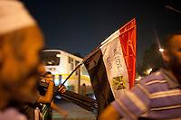 """EGITTO, IL CAIRO 9/10 settembre 2011: assalto all'ambasciata israeliana. Migliaia di manifestanti egiziani, ancora infuriati per l'uccisione di cinque guardie di frontiera egiziane da parte dell'esercito israeliano, hanno fatto irruzione nella sede diplomatica israeliana e sono stati poi sgomberati da esercito e polizia egiziana. Nell'immagine: manifestanti con bandiere dell'Egitto su cui è scritto """"Noi amiamo l'Egitto"""". Sullo sfondo un autobus.<br /> Egypt attack to the Israeli embassy  Attaque à l'ambassade israelienne Caire"""