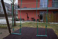Switzerland. Canton Zürich. Andelfingen. Apartment building. Each building has its own fallout shelter to accommodate people living with flats above. Green swings and a giraffe used as decoration. Winter foggy day. The giraffe (Giraffa) is a genus of African even-toed ungulate mammals, the tallest living terrestrial animals and the largest ruminants. 5.02.2019 © 2019 Didier Ruef<br /> <br /> .