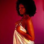 African American woman holding up pink satin sheet