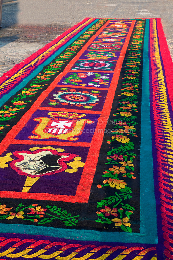 Antigua, Guatemala.  An alfombra (carpet) of colored sawdust, pine needles, and other traditional materials decorating the street in front of the Ayuntamiento (town hall, or Casa del Cabildo) in advance of the passage of a procession on Good Friday morning, La Semana Santa.  The alfombra will be finished only a couple of hours before the passage of the procession, after which the remains will be quickly swept away by municipal street sweepers.