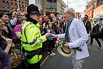 © Joel Goodman - 07973 332324 . 29/08/2015 . Manchester , UK . The actor , SIR IAN MCKELLEN , gives a flower to a policeman as he leads the 2015 Manchester Pride parade . Photo credit : Joel Goodman