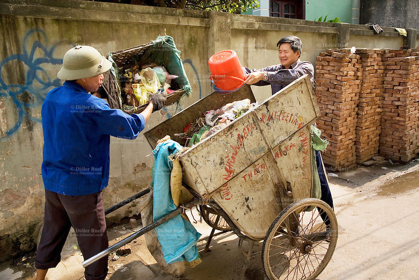 Vietnam. Ha Tay province. Lai Xa. A local worker of the village's cooperative running the collection and the waste disposal service, a man pour trash into the rubbish cart. The local project committee is in charge at a local level of a flexible decentralized community sanitation project (solid waste and wastewater management in a system based on houselhold participation and community involvement, as a decentralized sanitation implementation). Waste collection is an important requisite to prevent rubbish from clogging the new drainage and sewage system. Lai Xa is a typical hamlet (village) of the Red River delta region and is part of the Kim Chung commune located 15 km west of Hanoi. The peri-urban location is under increasing pressure of urbanization. 07.04.09  © 2009 Didier Ruef