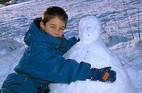 Young boy hugging a snowman.