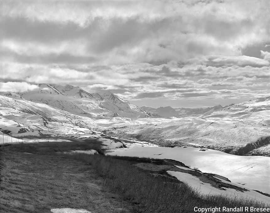 """""""Thompson Pass""""<br /> Alaska<br /> <br /> The Richardson Highway connects Valdez and Fairbanks, Alaska. The highway climbs through Thompson Pass 26 miles north of Valdez. Thompson Pass receives more snow than any location in Alaska, averaging 551 inches per year. This black and white photograph shows snow in the pass during May 2016."""