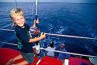 Young boy sports fishing on a family vacation, Kona, Hawaii