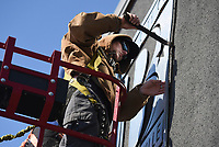 Sign installer Daniel Ward removes a sign, Friday, February 19, 2021 at the old Bentonville City Hall in Bentonville. The signs will be repurposed to other city buildings. Check out nwaonline.com/210220Daily/ for today's photo gallery. <br /> (NWA Democrat-Gazette/Charlie Kaijo)
