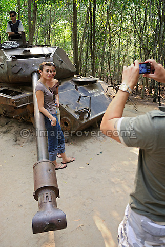Asia, Vietnam, Cu Chi nr. Ho Chi Minh City (Saigon). Cu Chi Tunnels. Tourists posing for a photo at an US american M41 tank that was destroyed by a delay mine in 1970.