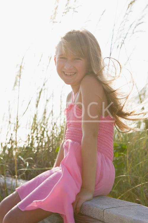 USA, Florida, St. Pete Beach, Portrait of girl (8-9) sitting on wooden rail on beach
