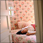 Woman laying on bed in floral wallpapered bedroom